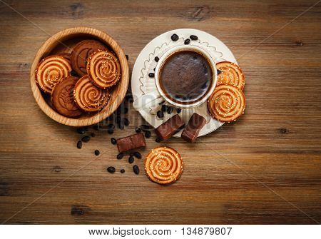 There are Cookies,Candy,Chocolate Peas,Poppy;Porcelain Saucer and Cap with Coffe,Tasty Sweet Food on the Wooden Background,Top View poster