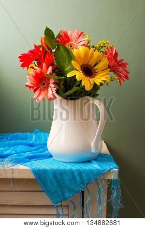 Beautiful gerbera flower bouquet on white table over green background