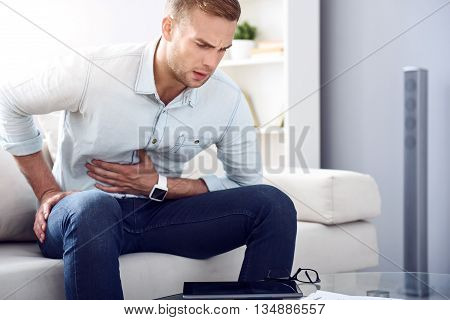 Need urgent help. Sick man sitting on the couch and writhing and feeling pain