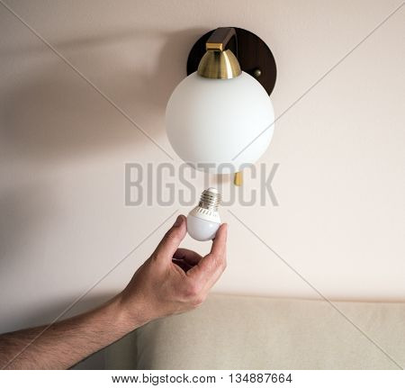 Man changes an electric light bulb energy efficiency. Closeup of man's hand adjusting electric bulb by pendant lights at home.