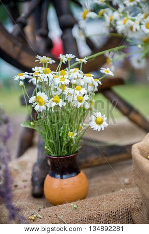 A bouquet of flowers is in a vase. Daisies are in ceramic vase handmade outdoors. Decoration at the fair - a bouquet of flowers in a ceramic vase
