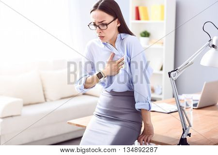 Sudden attack. Beautiful sick woman holding her hand on the heart and feeling pain while leaning on the table
