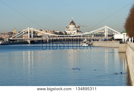 View from Moskva-river on Crimean bridge and Christ the Savior Cathedral in Moscow under clear blue sky