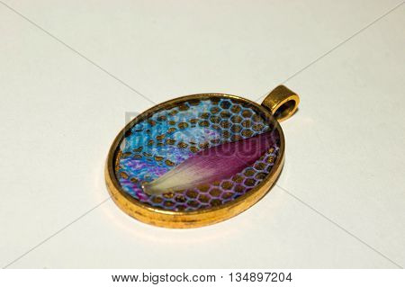 Brass color pendant with blue lace and gerbera petal inside the epoxy resin.