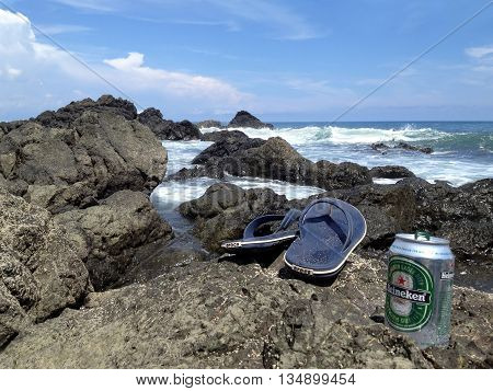 MONTEZUMA COSTA RICA - SEPTEMBER 16 2015: Heineken beer and Crocs flip-flops on the beach at Montezuma beach in Costa Rica