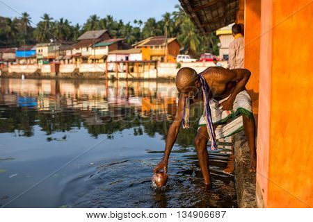 Gokarna, India - January 16, 2016: Unidentified temple brahmin taking water for puja from sacred lake in Gokarna. The city is a holy pilgrimage site for Hinduists