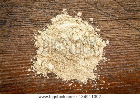 heap of red maca root powder against rustic weathered wood