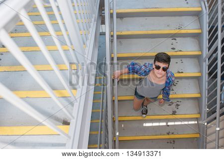 Teenage girl with crew cut looking up from stairs.