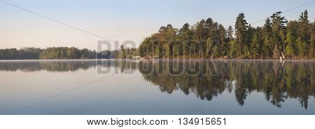 A panorama of a typical northern Minnesota lakeshore on a calm morning during Spring