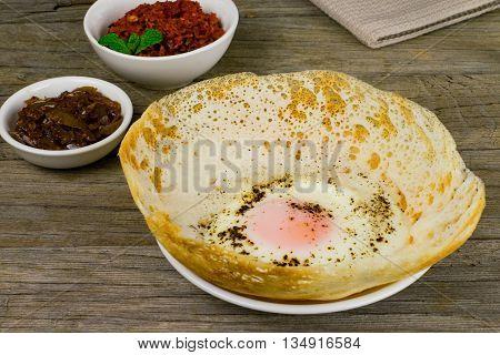 Sri Lankan style egg hopper with lunu miris and seeni sambal wooden background