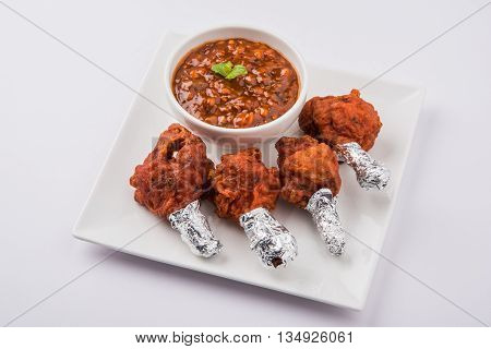 chicken lolipop, chicken winglet, tandoori chicken. Famous indian non veg dish, roasted chicken covered with silver foil, served with spicy chutney, indian chinese appetizer poster
