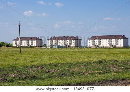 Village Morshanskoe Kargatskiy rayon Novosibirskaya oblast Siberia Russia - June 12 2016: new modern three-storied apartment house on the outskirts of the village