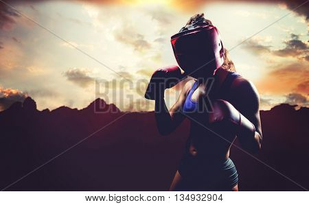 Portrait of female fighter with fighting stance against composite image of landscape