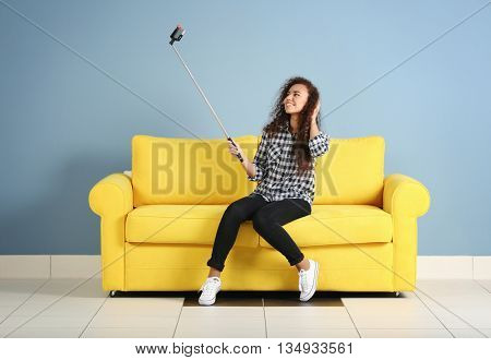 Young attractive woman taking selfie on yellow sofa in the room