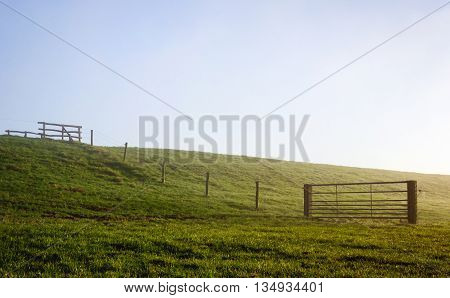 Backllit image of a Dutch dike with a fence and gates early in the morning at the beginning of the spring season. The morning fog has not disappeared yet.