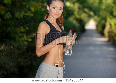 Beautiful girl, young athlete, brunette with brown eyes, beautiful smile, wearing a short black sports shirt and gray shorts, resting in a park after jogging in a hand holding a bottle of water, listening to music on headphones white