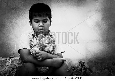Kid pauper with old teddy bear sitting near the concrete wallblack and white tone