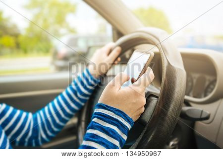 Woman driving car and texting message on smartphone using mobile phone device while driving dangerous and risky behavior in traffic