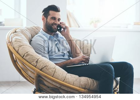 Working at home. Cheerful young handsome man working on laptop and talking on the mobile phone while sitting in big comfortable chair at home