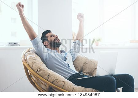 I did it! Handsome young man keeping arms raised and looking happy while sitting in a big comfortable chair at home with laptop laying on his knees