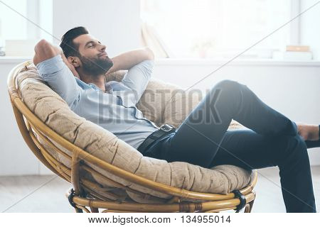 Total relaxation. Handsome young man keeping eyes closed and holding hands behind head while sitting in big comfortable chair at home