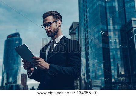 Modern businessman in the city. Night time image of confident young man in full suit holding digital tablet and looking at it while standing outdoors with cityscape in the background