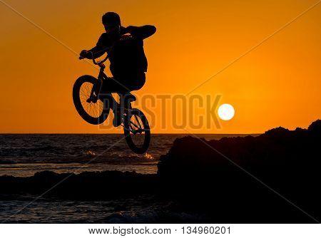 extreme sport bmx jump on a sunset background