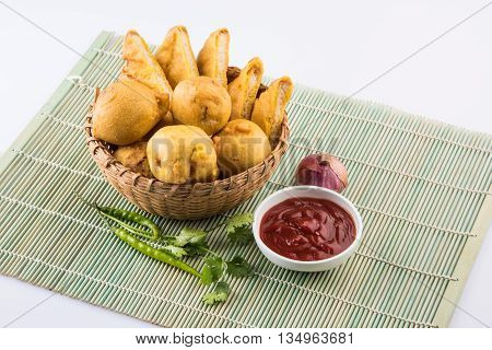 batata vada or aalu bonda or aalu bonde and bread pakoda or bread pakode served in a cane basket with tomato ketchup, onion and coriander over white background, isolated