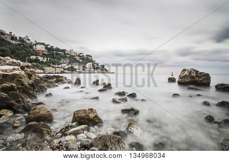 France, Nice, Cote d'Azur -Rocky beach in a long exposure shot