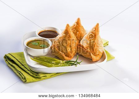 samosas or samosa - Indian deep fried snack, served with chutney and fried green chilly