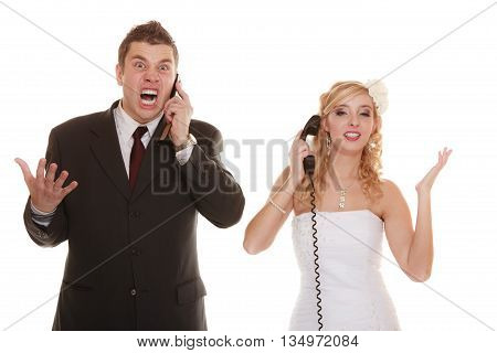 Wedding relationship difficulties. Angry woman and fury man talking on phone. Couple bride groom quarrelling screaming isolated on white.