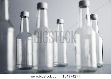 Set of empty cristal unlabeled bottles randomly presented on gray surface, isolated, close focus on backward bottles