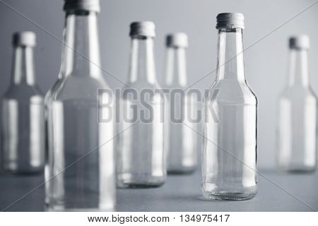 One focused empty clear transparent glass bottle for wine presented on right side and many unfocused bottles near, isolated on gray