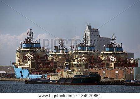 FREDERICIA DENMARK - JUNE 5 2016: Eight Maersk supply services offshore-ships berthed in Fredericia harbor. In front Tugboat Sigyn.