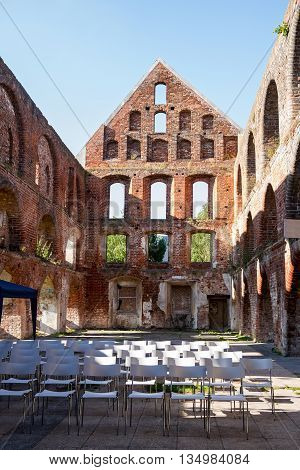 inside a brick ruin of a medieval monastery without roof with seating arrangements for an open air event concert and theater Bad Doberan northern Germany vertical