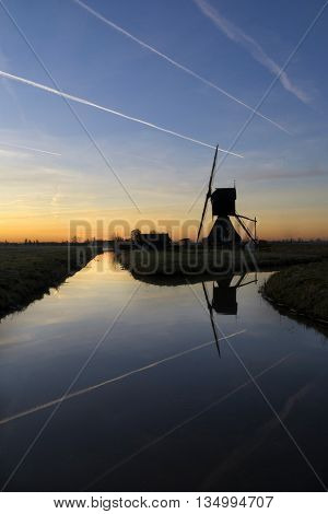 Contrails above the Scheiwijkse mill near Hoornaar in the Dutch region Alblasserwaard