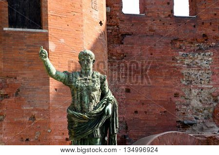 The ancient Roman walls and the statue of Julius Caesar in Turin