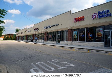 NAPERVILLE, ILLINOIS / UNITED STATES - JULY 23, 2015: A Naperville strip mall includes Baskin Robbins' ice cream, Dunkin' Donuts, Athletico Physical Therapy, GNC General Nutrition Center, a UPS store, a Subway restaurant, etc.