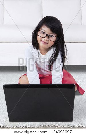 Photo of adorable little girl wearing glasses and smiling at the camera while using notebook computer on the carpet at home