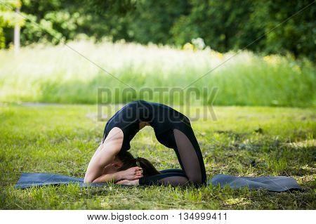 Portrait of beautiful sporty fit blond young woman doing bikram yoga backbend on summer day, Natarajasana, full length.