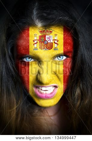 Portrait of a woman with the flag of the Spain painted on her face.