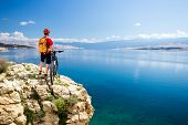 Mountain biking rider with bike looking at inspiring sea and mountains landscape. Man cycling MTB on enduro rocky trail path at sea side. Summer sport training fitness motivation and inspiration. poster