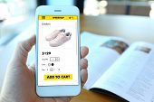 Hand holding smartphone with choose shoes on ecommerce website poster