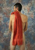 Nude muscular man with a red towel. poster