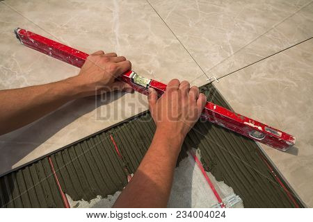 Ceramic Tiles And Tools For Tiler. Worker Hand Installing Floor Tiles. Home Improvement, Renovation