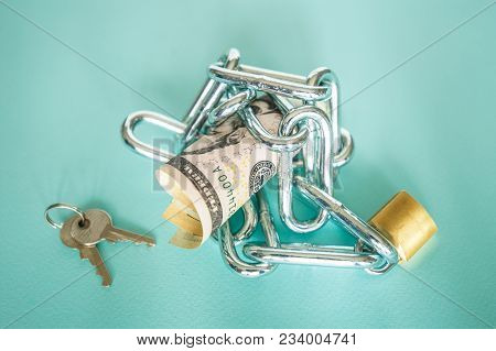 Cash Dollars Are Chained In A Chain With A Lock And With Keys As A Concept Of Saving Spending. The P