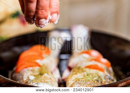 Close Up Hand Adds Spices To Fresh Pike Perch On Frying Pan. Cooking Concept