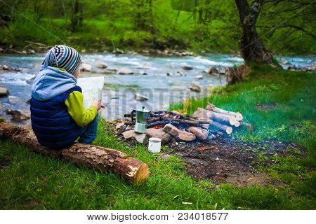 The Boy Sits On The Bank Of The River Near The Bonfire And Holds The Map, Near The Fire Is A Mug And