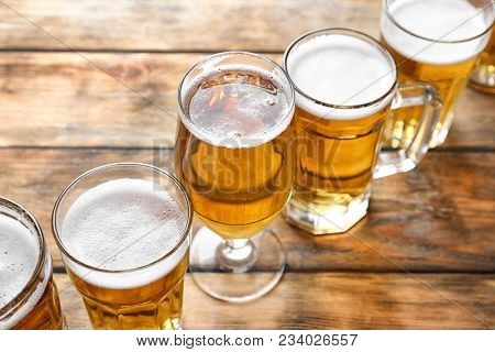 Glassware with fresh beer on wooden background