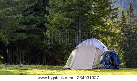 Tourist Camp On Green Meadow With Fresh Grass In Carpathian Mountains Forest. Hikers Tent And Backpa